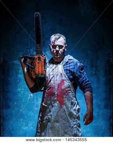 Bloody Halloween theme: crazy killer as bloody butcher with electric saw on dark blue background