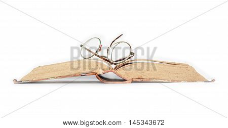 Vintage spectacles on old book against white background