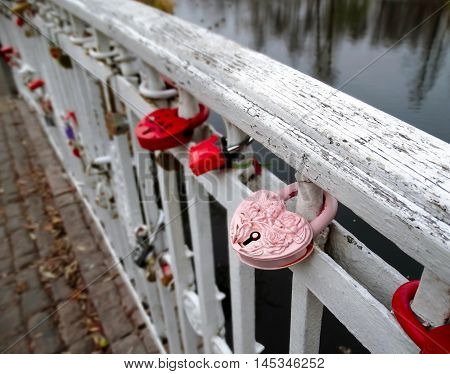 Romantic pink memory door-lock clipped on white handrail of a bridge in a park in November