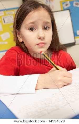 Schoolgirl Working In Classroom Under Pressure