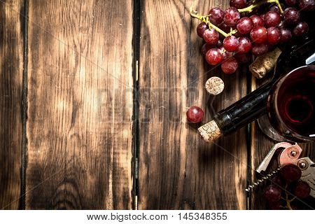 Red wine with a sprig of grapes and a corkscrew. On a wooden table.