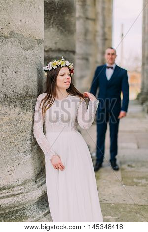 Young wedding couple standing outside near atique building with columns.