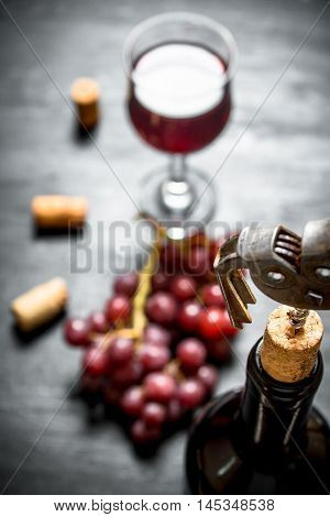Bottle of red wine with a corkscrew. On a black wooden background.