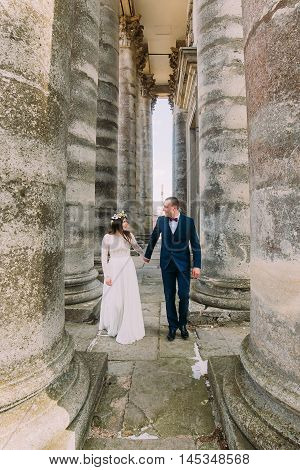Young newlywed couple posing between rows of antique building columns.