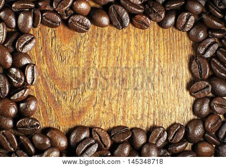 Coffee beans stacked in a frame on a wooden background