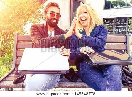 Creative business couple hands up doing high five outdoor - Cheerful hipsters holding pc laptop and gesturing in a city park - Concept of teamwork and fun together at sunset light with vintage filter