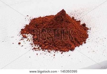 Bunch of red paint powder on white serviette