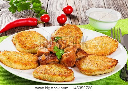 potatoes pancakes with stewed pork meat on white dish fork and knife on green table mat sour cream in gravy boat on old wooden background close-up