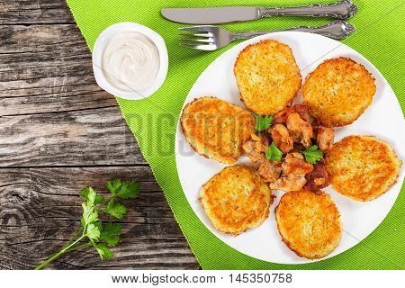 potatoes pancakes with stewed pork meat on white dish fork and knife on green table mat sour cream in gravy boat on old wooden background top view