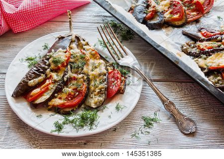 Baked eggplant in a fan shape on a white plate and baking sheet. Wooden background. Cooked with tomatoes and cheese. Sauce - olive oil garlic dried oregano and basil sprinkled with fresh dill.