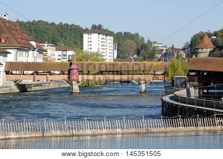 LUCERNE SWITZERLAND - MAY 05 2016: Needle Dam in the river Reuss was designed to maintain the level of water in Lake Lucerne and Spreuer Bridge that is one of two extant wooden footbridges in Luzern