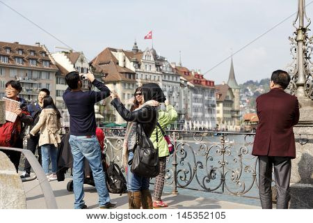 LUCERNE SWITZERLAND - MAY 02 2016: Unidentified tourists take pictures from the footbridge in the old town that offers variety of sightseeing attractions.