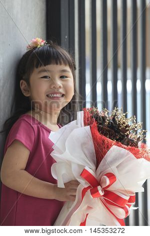 toothy smiling face of asian kid happiness emotion and dry flowers bouquet