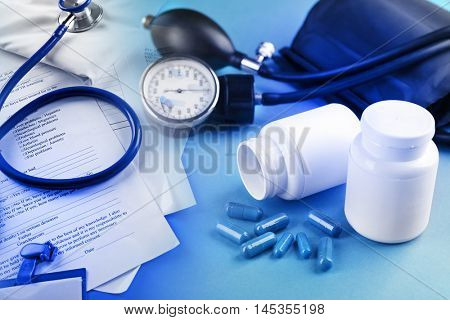Medical manometer and pills on blue background