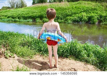 Boy with toy lifebuoy for swimming outdoors in the summer on a sunny day