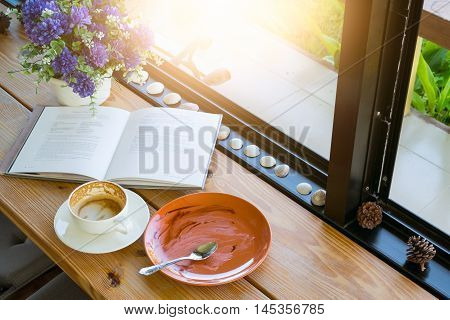 Empty Coffee Cup And Empty Plate After Drink Coffee And Cake With Book On Wooden Desk.