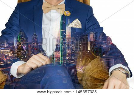 Man in blue suit with coffee cream bowtie color flower brooch and dot pattern pocket square sitting on cozy sofa. Double exposure with big city building night time. Socialize man. Sophisticated city life.