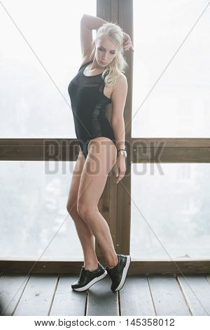 sports girl in a black body at the window standing on tiptoes