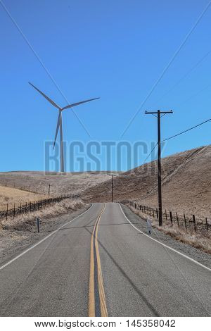 Country Road, with Two Lanes, a Wind Turbine, power poles and blue sky
