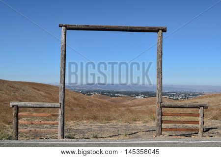 Old Wooden Framed Entrance to Farmland, with a blue sky and mountain range in the distance