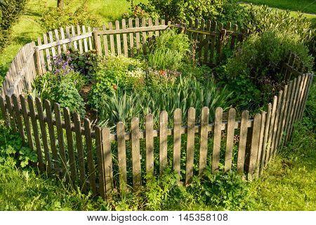 idyllic small flower garden fenced octagonal wooden fence