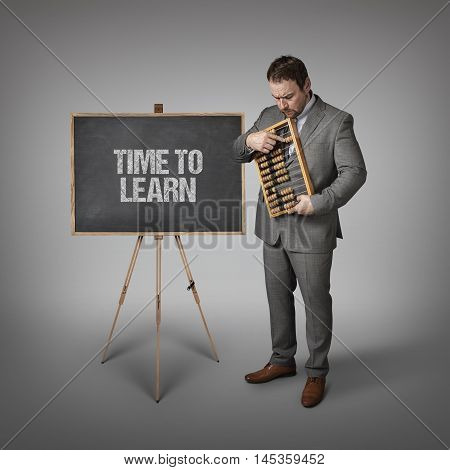Time to learn text on blackboard with businessman and abacus