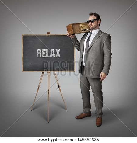 Relax text on blackboard with businessman holding radio