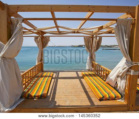 Wooden pagoda on a beach of luxury tropical resort with mattresses and sea view