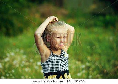 Little girl crying , on summer street . Closeup portrait