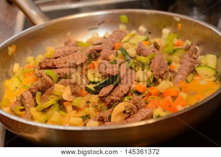 In saucepan beef cooked with vegetables - closeup