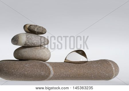 stacked rounded stone pebble arrangement with fluid drop in light grey back