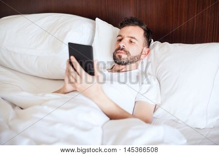 Man Reading An E-book In Bed