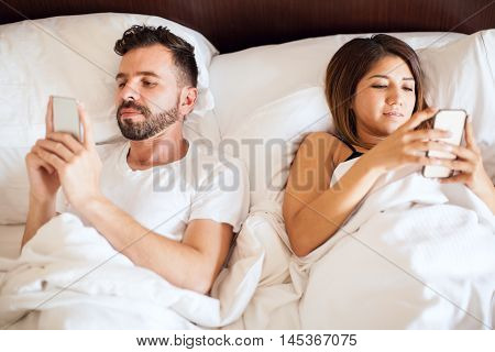 Young Couple Using Their Phones In Bed