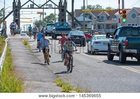 Manasquan NJ US -- September 2, 2016. Bicyclists come from over a bridge on a summer morning. Editorial Use Only.