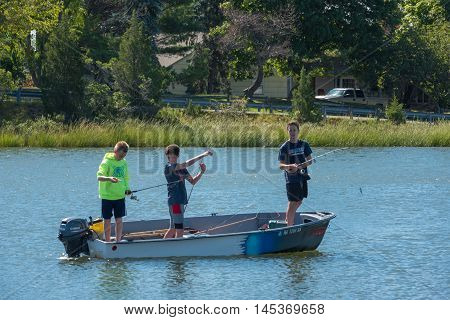 Manasquan NJ US -- September 2, 2016. Boys fishing from an outboard motor boat on the inlet. Editorial Use Only.