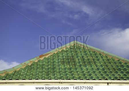 Green roof tiles set against blue sky with wispy clouds providing copy space.