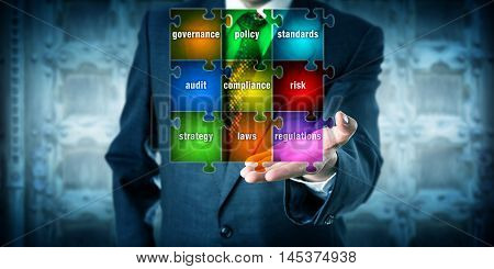 Male GRC management professional presenting a virtual planning matrix in form of a jigsaw puzzle in his left palm of hand. Business concept for corporate governance risk management and compliance.