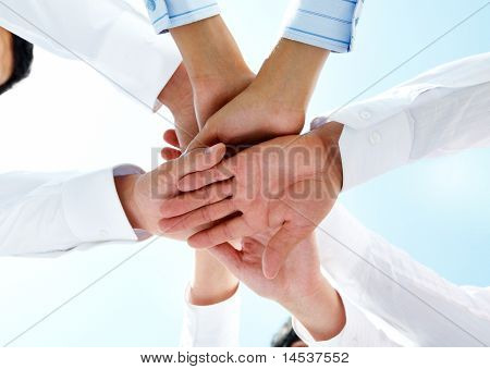 Bottom view of people hands holding together on a sky background
