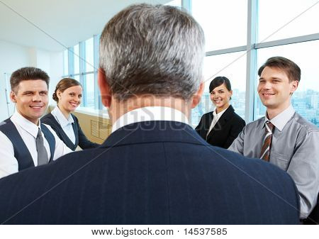 Rear view of aged businessman making report to partners at conference