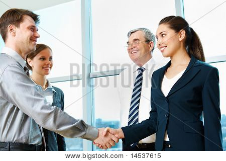 Photo of successful partners handshaking after signing agreement at meeting