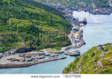 At the entrance to St John's Harbour in Newfoundland Canada.  Boats docked in harbour.   Houses at the foot of the mountain, local workplaces.