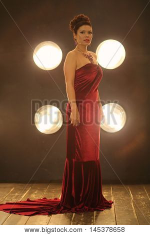 Young beautiful woman poses in red dress near wall with lamps in studio