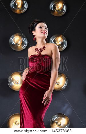 Pretty girl poses in velvet long dress near wall with lamps in studio