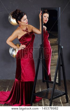 Woman in red looks away near mirror in studio with lamps on wall