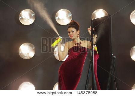 Woman in red poses with hair spray near mirror in studio with lamps on wall
