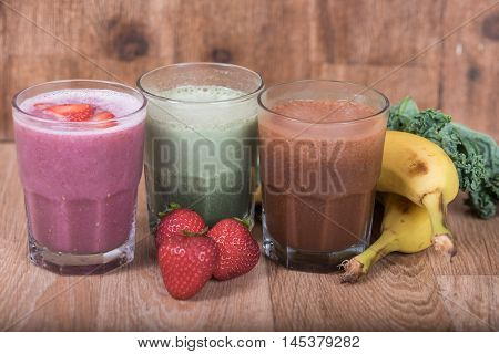 Three smoothie shakes in glasses on wood backgrounds