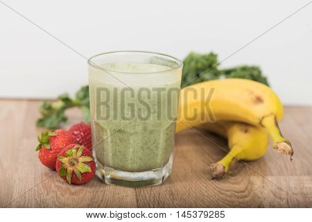 Green smoothie shake with bananas strawberries and Kale