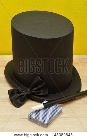 A magicians hat displayed with a wand bow tie and a deck of cards
