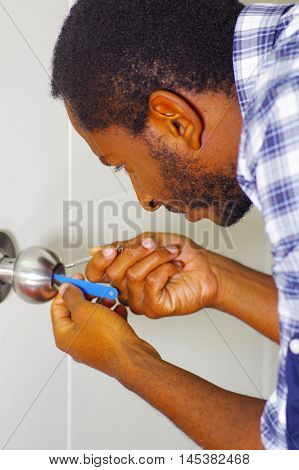 Closeup head and hands of locksmith using pick tools to open locked door.