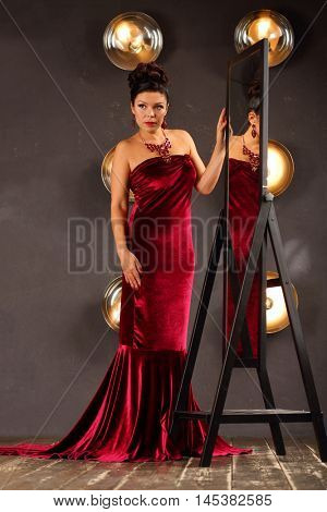 Woman in red poses near mirror in studio with lamps on wall